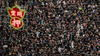 Protesters hold banners and shout slogans as they march on a street on June 16, 2019 in Hong Kong