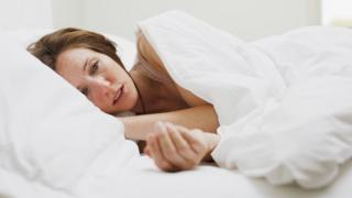 Sick woman with flu lying in bed
