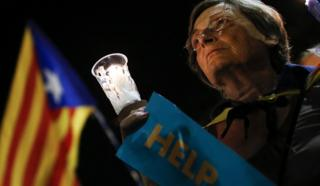 A woman holds a candle during a demonstration in Barcelona against the arrest of two Catalan separatist leaders, 17 October 2017