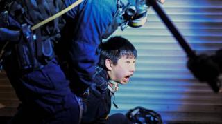Un policía sujetando a un manifestante en Hong Kong.