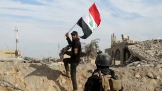 A member from the Iraqi security forces holds an Iraqi flag in the city of Ramadi, December 27, 2015.