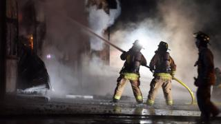 Firefighters spray water on a building