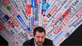 Salvini participa de coletiva de imprensa, com plano de fundo estampado com marcas de veículos de imprensa
