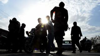 Afghan policemen search commuters at a checkpoint in Lashkar Gah, the capital of Helmand province. October 6, 2016