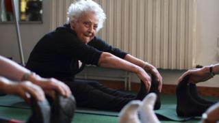 Older woman exercising with others