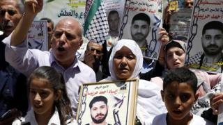 Palestinians hold posters in solidarity with Palestinians jailed in Israel at a protest in the West Bank city of Hebron (21 June 2018)