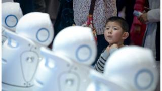 A boy looking at a display of robots during the World Robot Conference in Beijing