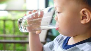 A boy drinking water out of a glass