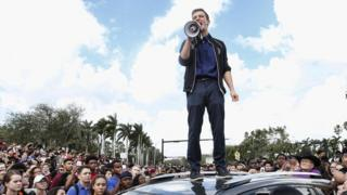 Cameron Kasky standing on a car