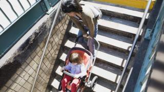 Woman taking buggy down steps