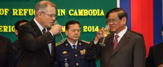 Australian Immigration Minister Scott Morrison and Cambodian Interior Minister Sar Kheng celebrate signing the deal with champagne (Sept 2014)