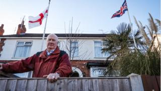 Ian Durrant with the Union Flag and the cross of St George in front of his house in Lincoln