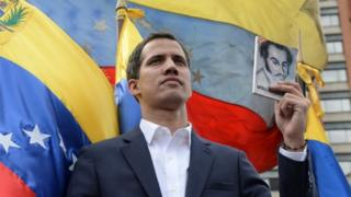 Juan Guaidó holds up the Venezuelan constitution in Caracas on 23 January 2019