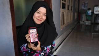 Ely Susiawati with a photo of her mother