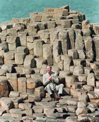 O príncipe Charles aparece sentado sozinho sobre pedras que compõem a Calçada dos Gigantes, um monumento natural na Irlanda do Norte