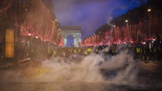 """Yellow vests"" (gilets jaunes) demonstrators stand amid tear gas on the Champs Elysees avenue in front of the Arc de Triomphe in Paris on December 8, 2018"