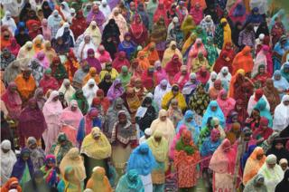 This photo taken on August 21, 2018 shows Indian women welcoming the Eid al-Adha festival with prayers near a shrine complex in Ahmedabad. - Muslims are celebrating Eid al-Adha (the feast of sacrifice), the second of two Islamic holidays celebrated worldwide marking the end of the annual pilgrimage or Hajj to the Saudi holy city of Mecca.