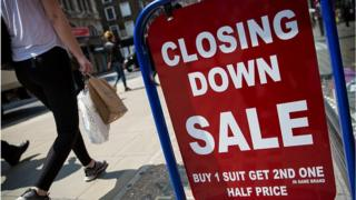 A closing down sale sign is seen outside a men's clothing shop on Oxford Street