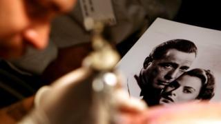 "Мастер тату рисует на коже клиента сцену из ""Касабланки"". 15 сентября 2006 года, Лос-Анджелес"