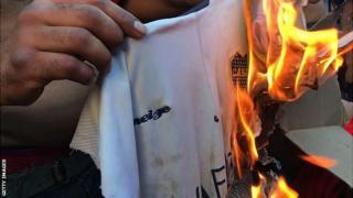 A River Plate fan sets a Boca Juniors shirt alight