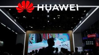 People walk past Huawei stall
