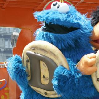 The Cookie Monster from Sesame Street holds up the letter D