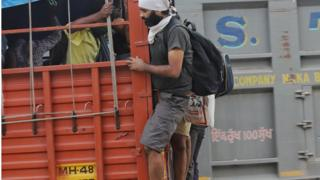 Two migrants hanging on the back of a truck