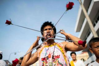 A devotee of the Loem Hu Thai Su shrine has a metal rods with roses pierced through his cheeks as he parades during the annual