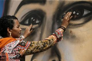 Sudanese activist Eythar Gubara holds her hands up to the eyes of a large, painted face on a wall. Her expression is thoughtful.