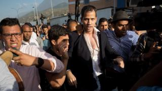 Guaidó at an airport near Caracas, having had his shirt ripped open by protesters