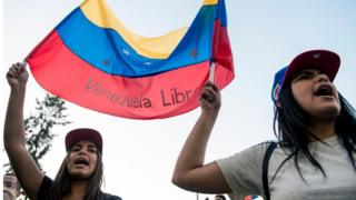 """Venezuelan citizens living in Chile shout slogans during a demonstration against president Nicolas Maduro""""s government in Santiago, Chile, on April 30, 2019"""