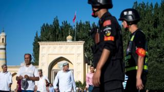 Police patrolling as Muslims leave the Id Kah Mosque in the old town of Kashgar in China's Xinjiang