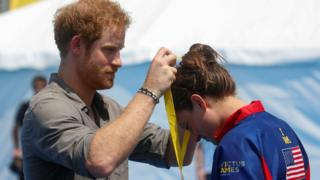 Prince Harry awarding a medal to a competitor