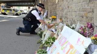 Londra'da bir polis Finsbury Park'ta hayatını kaybeden kişi anısına duvara çiçekler bırakıyor