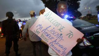 An Arsenal fan holds a poster to welcoming Former soccer coach Arsene Wenger upon his arrival at the Roberts International Airport in Harbel, Liberia, 22 August 2018.