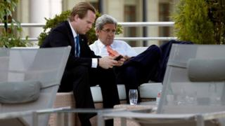 U.S. Secretary of State John Kerry (R) sits beside the hotel pool with aide Jason Meininger during a break from his meeting with Russian Foreign Minister Sergei Lavrov in Geneva