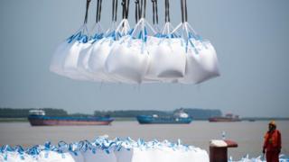 عمال يحملون سلعا كيميائية في ميناء صيني هذا العام