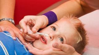 Flu Vaccine given intranasally by a nurse to a four year old patient.