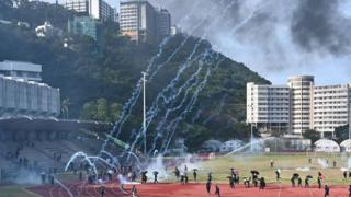 Protesters react after police fired tear gas at the Chinese University of Hong Kong (CUHK), in Hong Kong on November 12, 2019