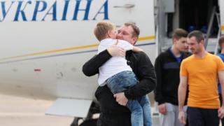 мальчик на руках у мужчины у трапа самолета