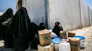 Perempuan di kamp Al-Hol, duduk di dekat kotak-kotak bantuan.