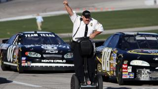 "Actor and comedian Kevin James celebrates while racing NASCAR stock cars with his Segway to promote the release of his new movie, ""Paul Blart: Mall Cop""."