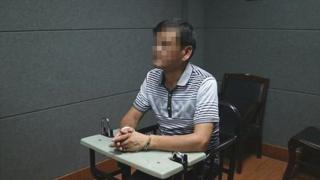 El escritor chino Liu Yongbiao bajo custodia policial sentado en una silla y con los brazos sobre una mesa