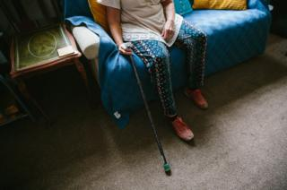 Jackie Cheetham sits at home with her walking stick