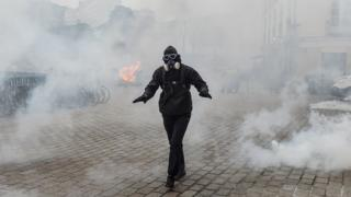 A protester dressed in black walks amid tear gas smoke during a protest against the pension overhauls, in Nantes, on 5 December, 2019.