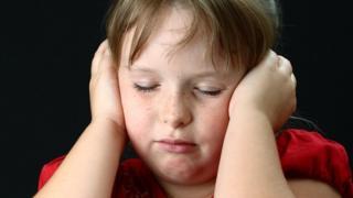 Criança com as mãos cobrindo os ouvidos