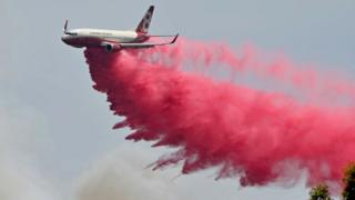 A Rural NSW Fire Service plane drops fire retardent on an out of control bushfire near Taree