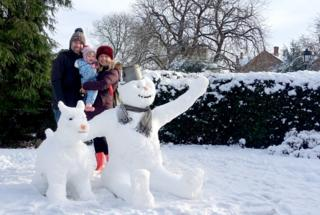 Snowman and dog with parents and daughter