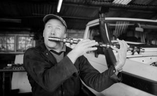 Man pretending a camshaft is a flute