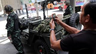Bir kişi cep telefonuyla Taylandlı askerin fotoğrafını çekiyor.